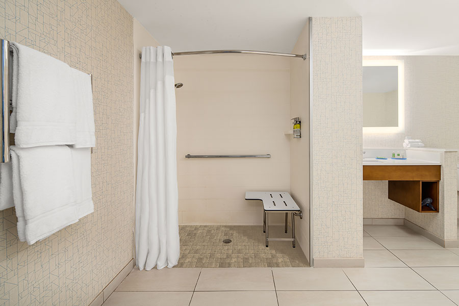 roll-in shower and grab bar in accessible guest bathroom