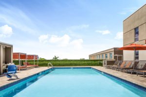 outdoor pool with lounge chairs and pool lift